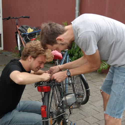 Zwei Reparateure reparieren zusammen ein Fahrrad.